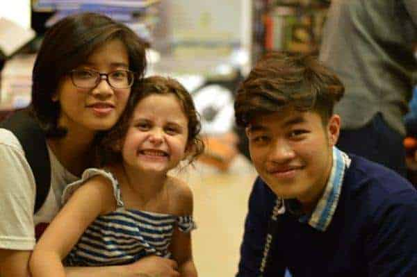 Two hanoikids tour guides with a young customer.