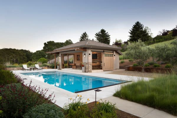 a transitional backyard amidst natural landscape featuring a modern pool and open-air pool house with bathroom