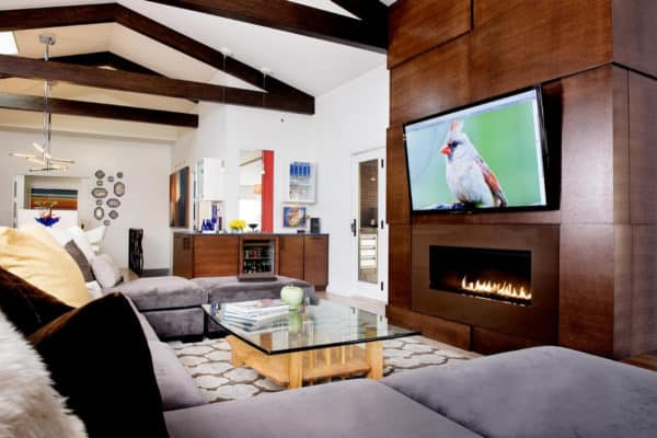 go for a contemporary open concept room with white walls, wood elements, linear fireplace, and tv