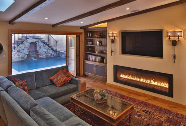 spanish-inspired mediterranean room featuring a long linear fireplace and mounted tv