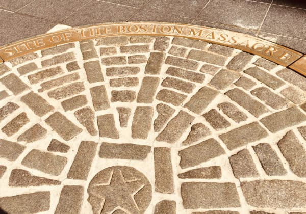 A sidewalk marker near quincy market notes the site of the boston massacre.