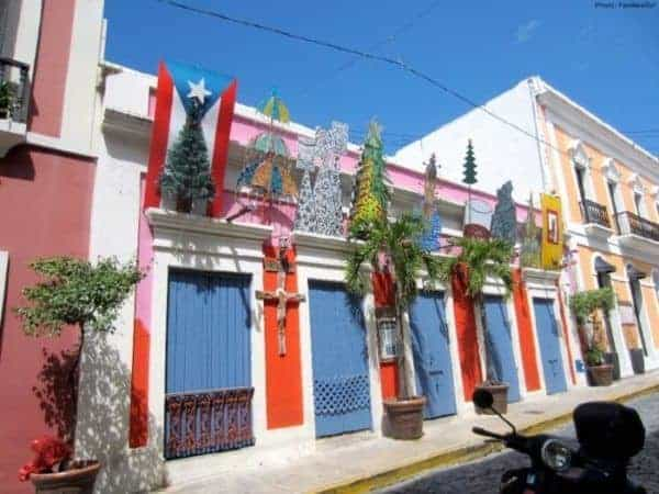 A typical street in old san juan with brightly colored houses and christmas type decorations.