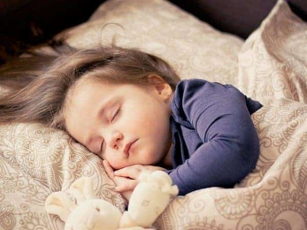 A toddler sleeping soundly in bed.