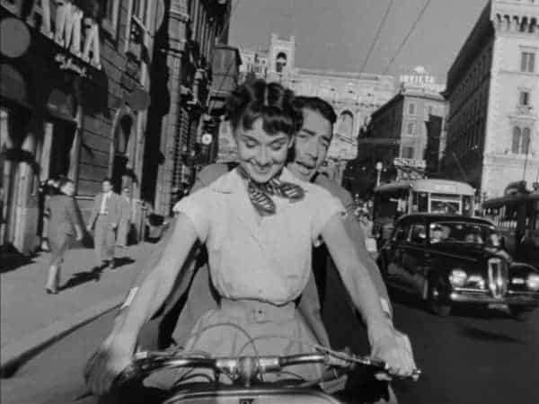 A princess and an american reporter see rome by vespa in roman holiday.