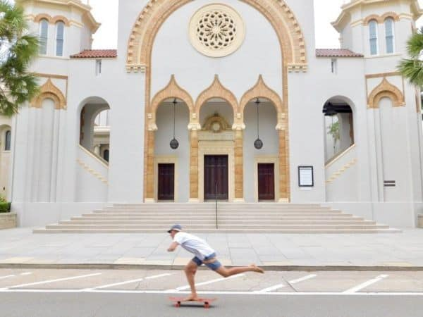 A barefoot skateboarder cruises by st. Augustine's gilded-age church on the way to the beach.