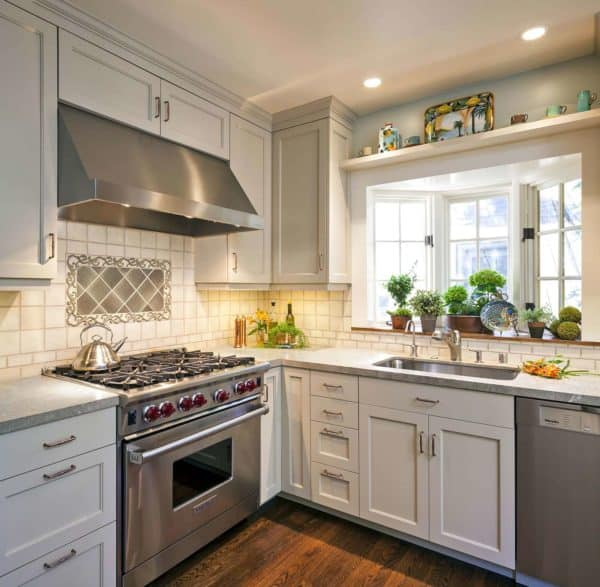 an elegant kitchen remodel featuring bay window over sink and limestone countertops