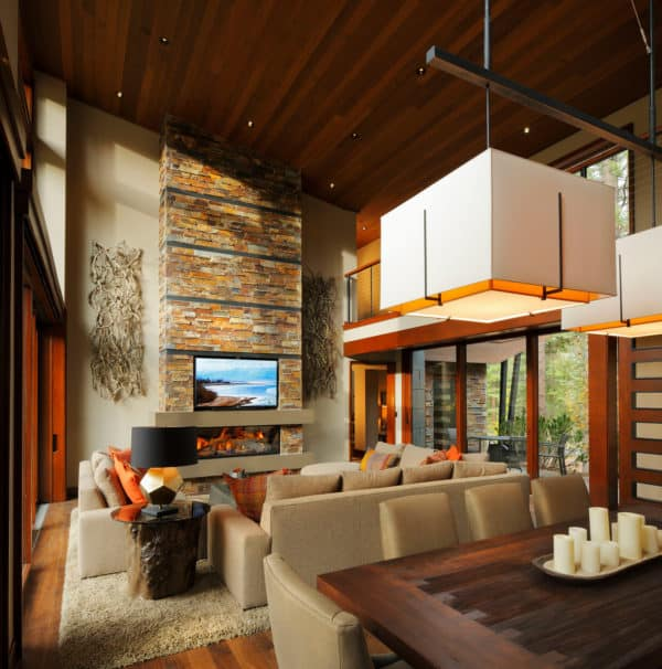 combine stone-clad linear fireplace with stunning tv in a dramatic mountain-style living and dining room
