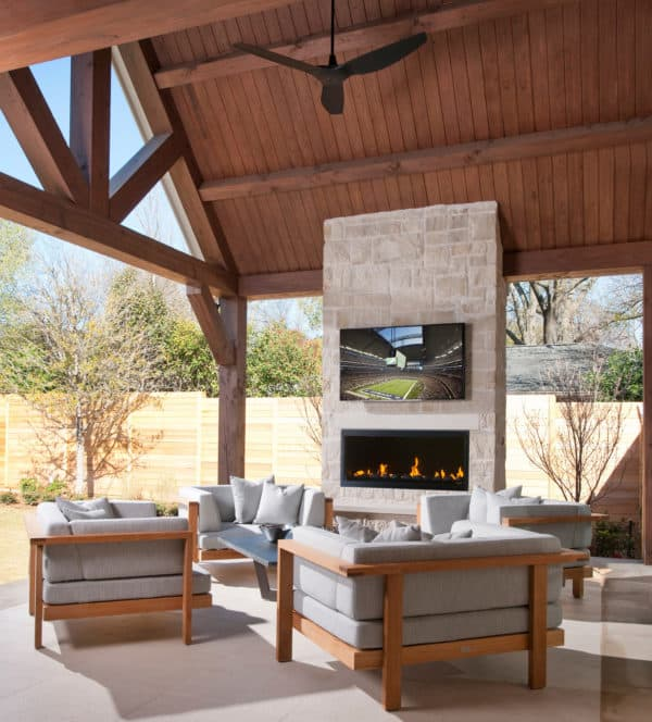 try a stone wall to hold linear fireplace with tv above in a charming semi-outdoor patio