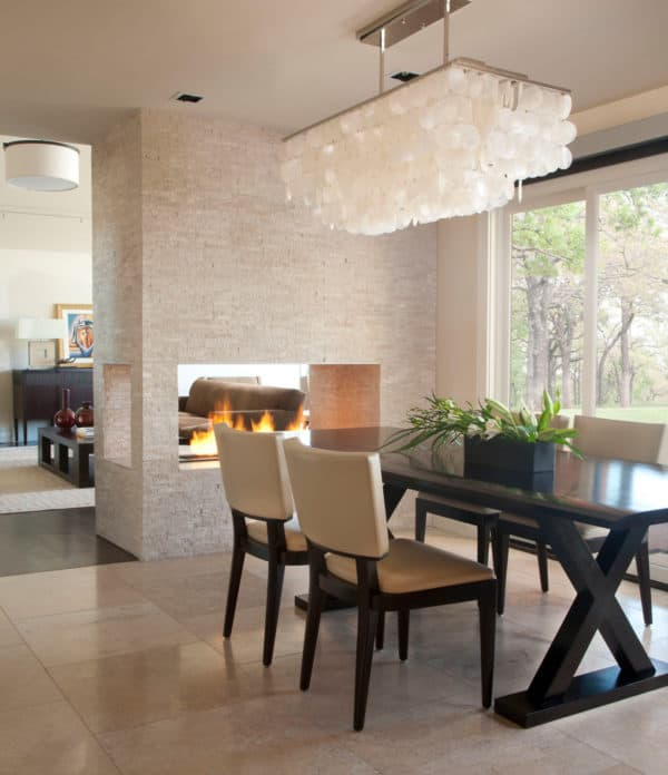 go classic and trendy with travertine and beige tile floors in front of luxurious fireplace