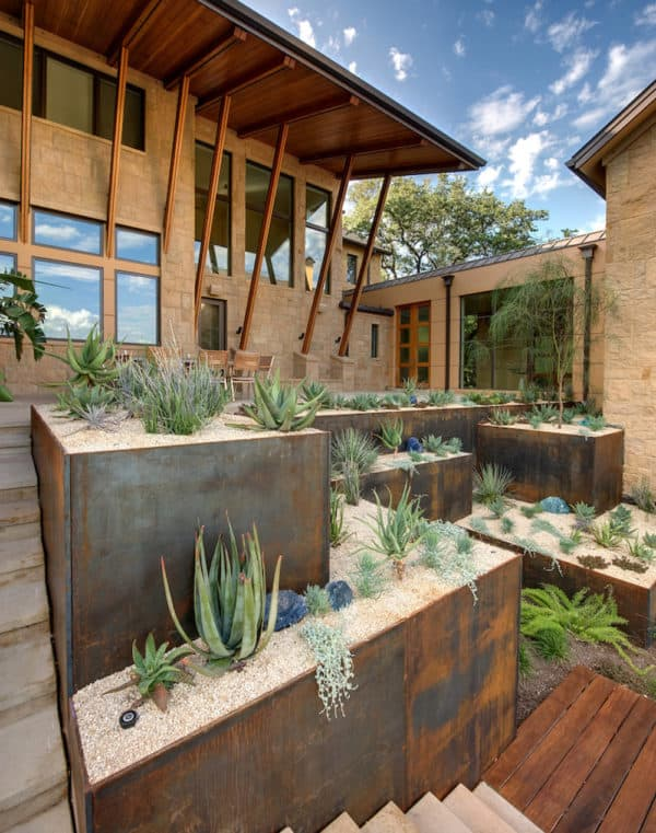 use corten steel retaining wall and concrete paver landscaping for a southwestern-inspired home