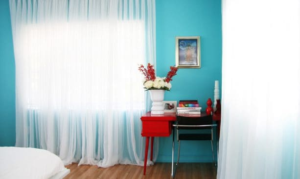 a red desk and turquoise wall in a contemporary bedroom