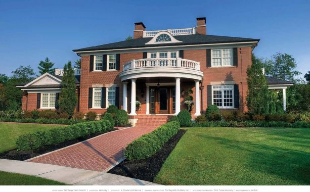 a red brick house with black roof and black shutters