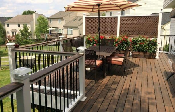 the combo of framed lattice and potted plants for deck rail screen