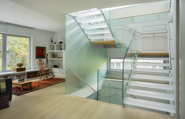 the combination of resin treads and glass railing in an open staircase