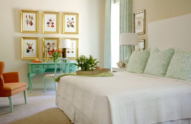 a turquoise desk and gold picture frames in a traditional bedroom