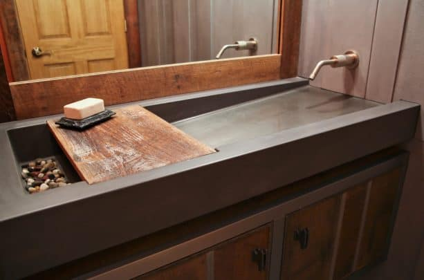 a contemporary concrete bathroom sink with colorful rocks on the drain