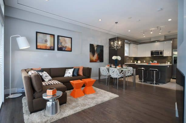open-style living room with wood brown sectional couch and small orange table color ideas