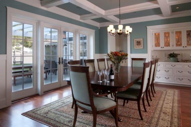 craftsman dining room design with exposed beams connected to the crown molding