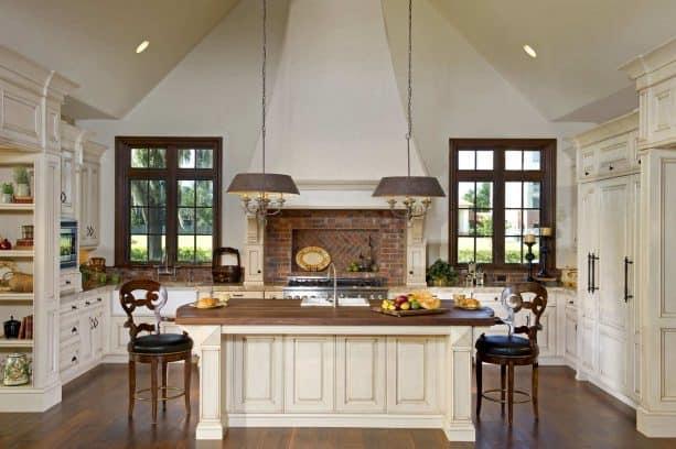 cream kitchen cabinets paired with red brick backsplash
