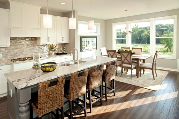 open transitional kitchen and dining room with light and warm grey walls and dark color hickory wood floor
