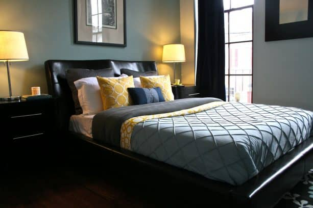 a contemporary bedroom with greyish blue walls and black curtain