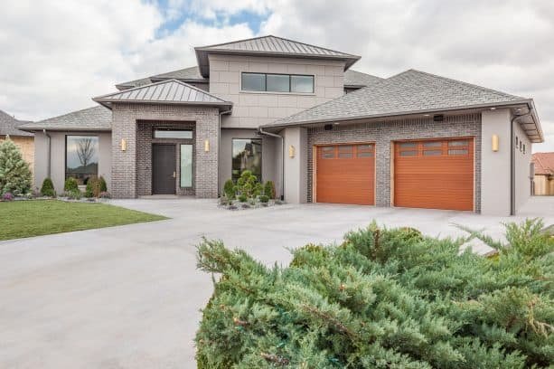 a grey stucco and brick house with bronze metal roof