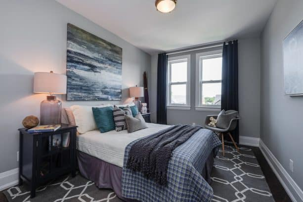 a black and grey contemporary bedroom with accentuating teal pillows