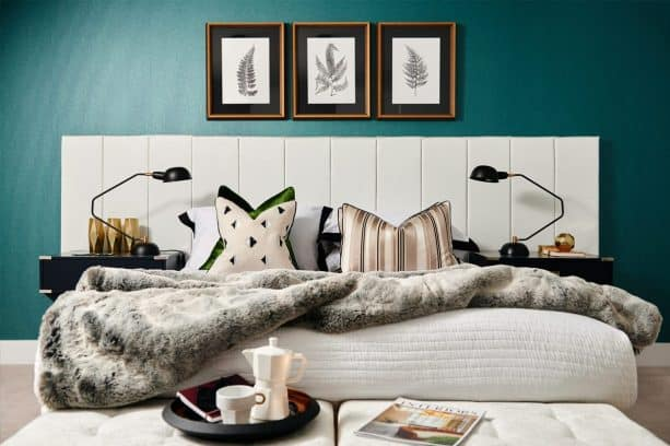 a white and black bed looks popping in front of a teal bedroom wall