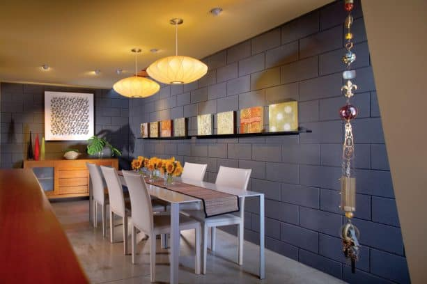 a contemporary dining room with grey cinder block walls