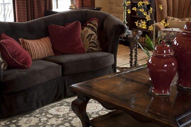 elegant contemporary living room with brown wood sofa with wine red pillows
