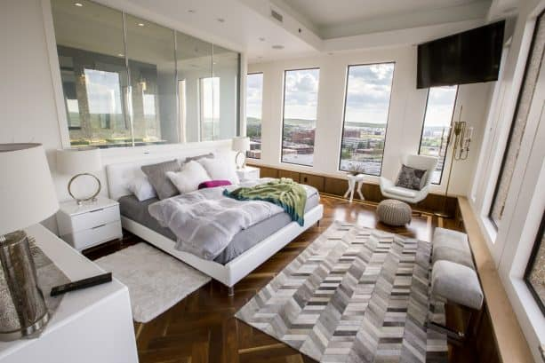 a grey and white bedroom with glossy dark hardwood floor