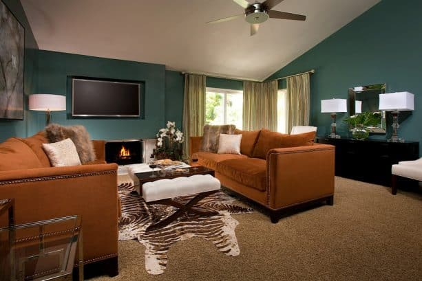 a living room with teal and rust color theme