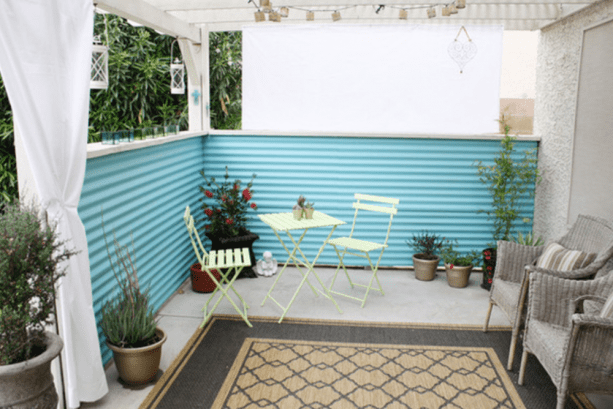eclectic patio with turquoise corrugated metal fencing
