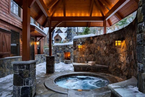 a hot tub in a sunken covered walkout basement patio