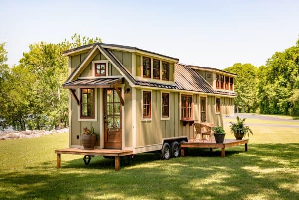 a tiny house with sage green walls, warm white trim, and wooden windows and doors