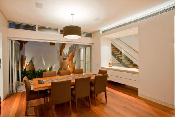 a dining room and a hallway separated with a large glass window