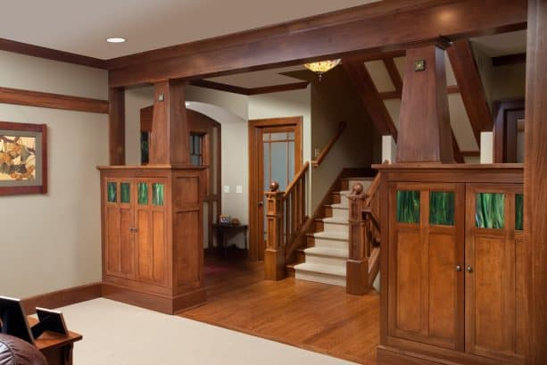 a craftsman entry with crown molding, tapered posts, and exposed beam