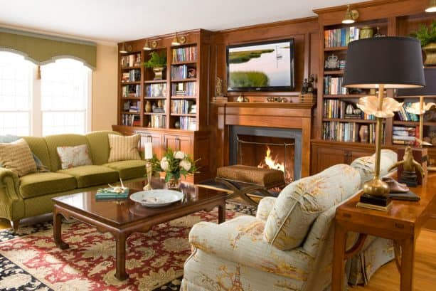 a strong and cozy traditional look resulted from the custom, stained wood fireplace and bookshelves