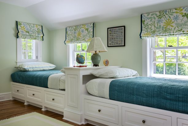 a shared kids' bedroom with sage green walls for gender neutral visual