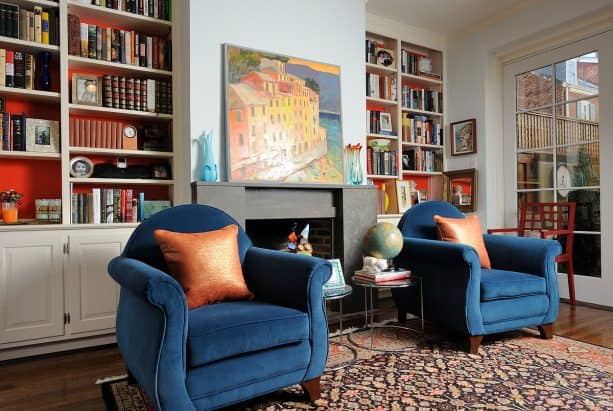 a simple black limestone fireplace paired with two built-in white bookshelves with orange back panels