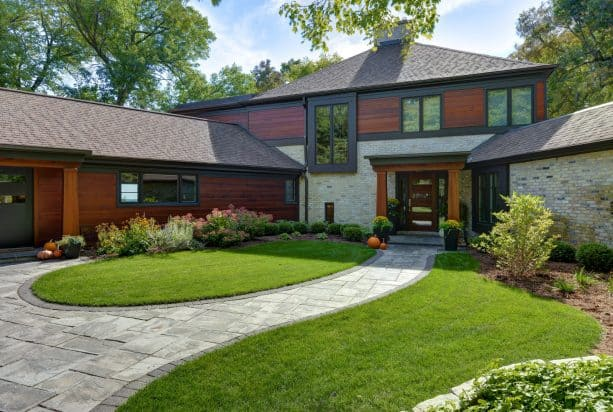 an aesthetic and elegant light contemporary exterior with the combination of dark-stained wood siding and tan brick