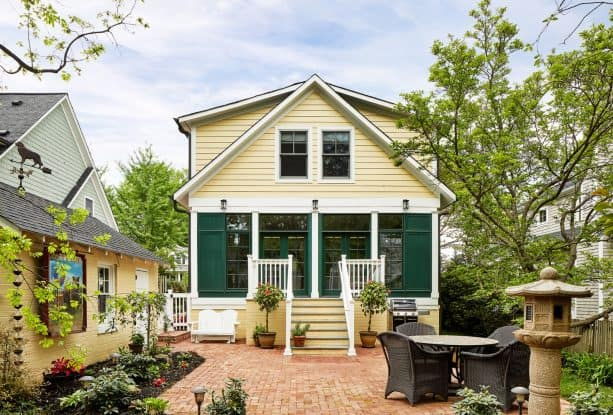 craftsman exterior with pale yellow siding, white trim, and dark green doors and windows