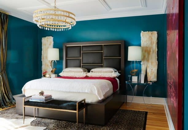 a transitional bedroom with elegant and bold teal walls, black headboard, and gold accents here and there