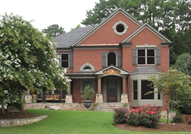 a red brick house with grey roof and grey shutters