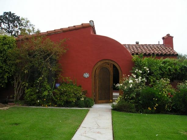 the combination of red stucco and wooden trim for creating a welcoming visual
