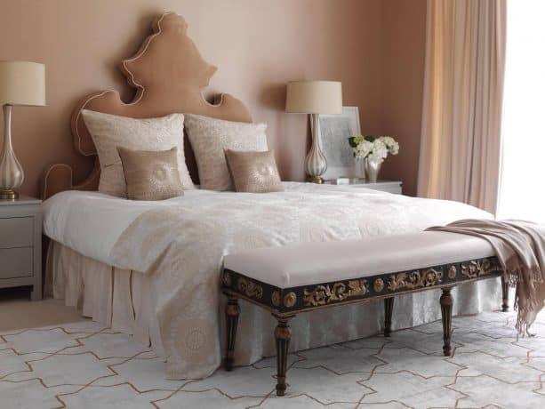 a contemporary bedroom with tan headboard and soft pink walls