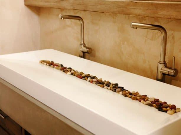 a white contemporary double-sink with colorful rocks in it