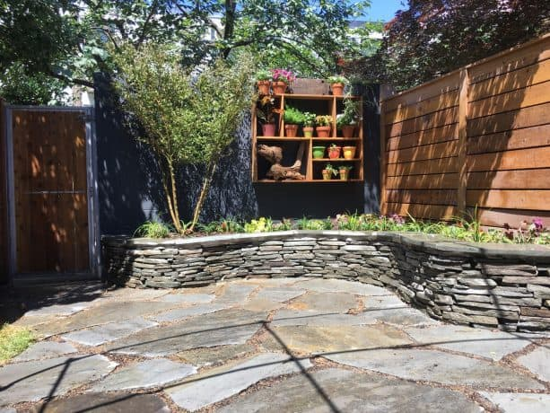 a cinder block wall is painted in slate grey color after a garden makeover