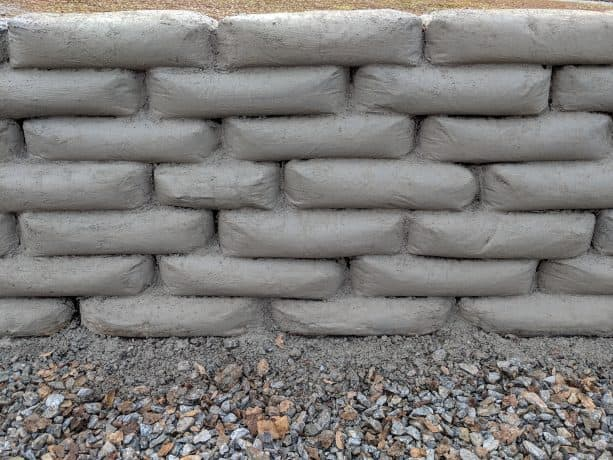 a retaining wall built by stacking Sakrete Concrete Mix bags