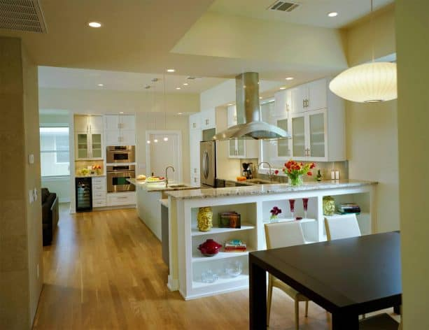 an open kitchen and dining room with a large half wall with built-in shelf